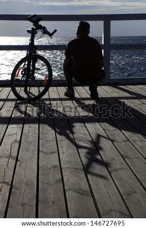 man bike at the pier, jetty in morning sea - stock photo