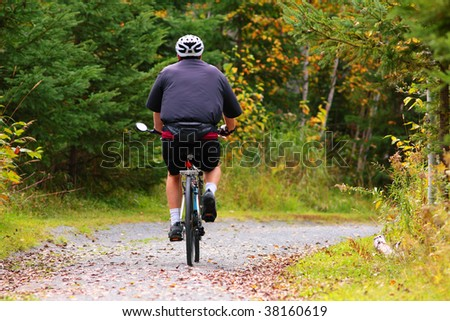 man biking threw the woods on local trail - stock photo
