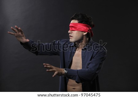 man blindfolded with red cloth - stock photo
