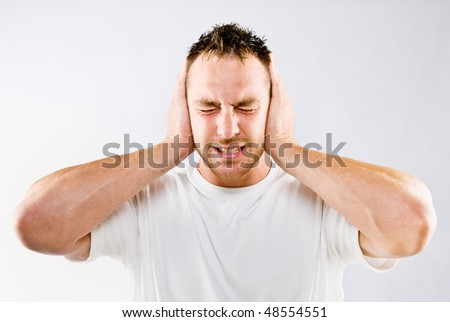 Man blocking out loud noise from ears