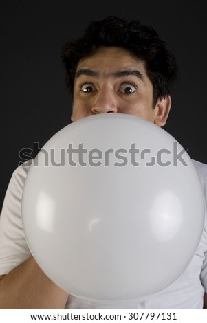 Man blowing air into a balloon - stock photo
