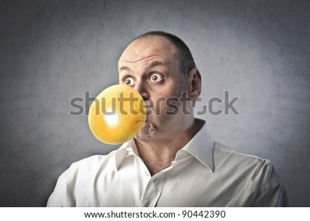Man blowing bubbles with a chewing gum - stock photo