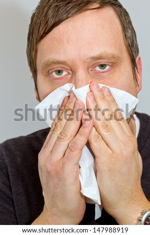 Man blowing his nose - stock photo