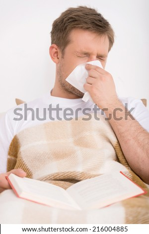 Man blowing his nose while lying sick in bed. man lying in bed and reading book - stock photo