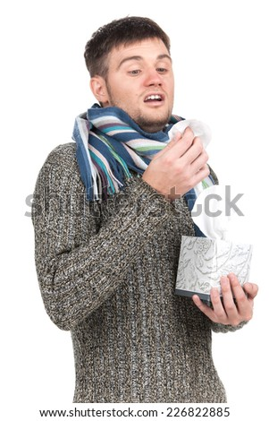 Man blowing into tissue and pulling tissues from box. exhausted allergic man standing on white background
