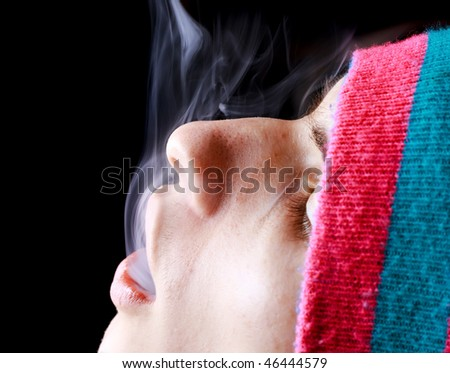 Man blowing smoke on a black background - stock photo