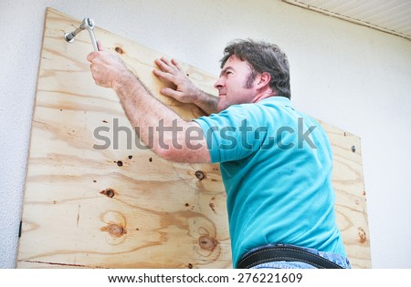 Man boarding up the windows on his home to prepare for a hurricane or tornado.   - stock photo