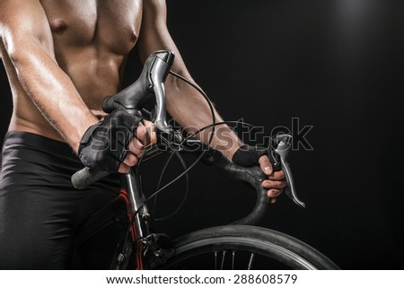 Man body sitting on bicycle in black studio