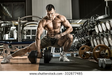 man bodybuilder , execute exercise with  dumbbells, inside gym, horizontal photo - stock photo