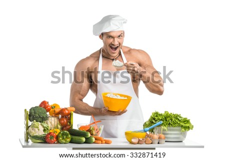 Man bodybuilder in white toque blanche and cook protective apron, eating cottage cheese , on whie background, isolated