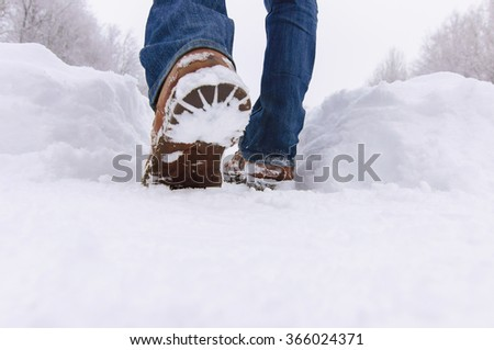Man boots in the deep snow a winter day. - stock photo