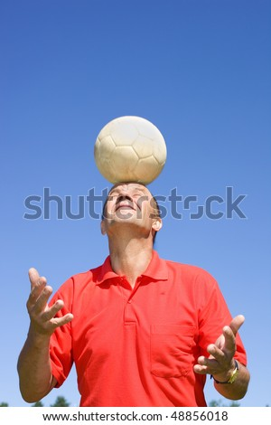Man bouncing football with his head - stock photo