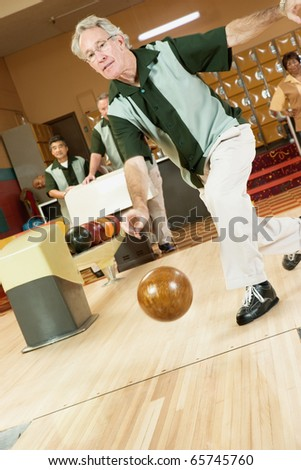 Man bowling at bowling alley - stock photo