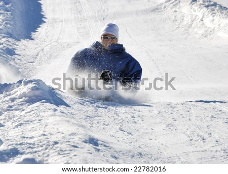 man braking while sledding fast down the hill with snow background - stock photo