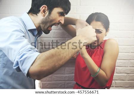 Man brandishing his wife. Family quarrel. - stock photo