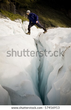 Man bridges the gap on a deep crevasse on a glacier, New Zealand