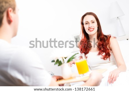 man brought his girlfriend breakfast in bed, holding a tray of juice and breakfast - stock photo