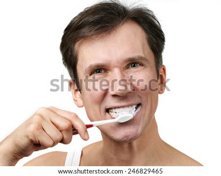 Man brushing his teeth on white background - stock photo