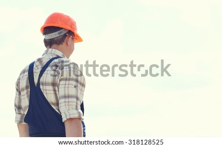 Man builder. Handyman with a tool belt. Male builder. Construction worker. Construction worker on a construction site. Renovation, service. Worker looking at a building site. Toned image. - stock photo