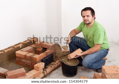 Man building a brick stove - holding trowel with clay mortar