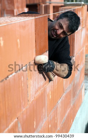 Man building a brick wall - stock photo