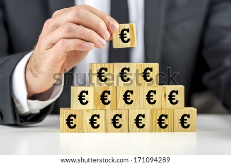 Man building a pyramid of euro symbols on wooden building blocks placing the last cube on the top, conceptual of business success and growth or of the global economic situation within the EEC - stock photo