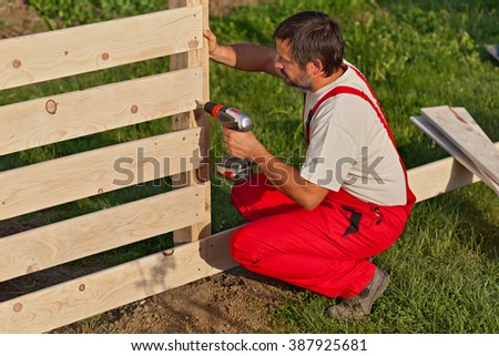 Man building a wooden fence - fastening the boards with screws - stock photo