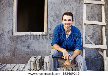 man building or repairing his house - stock photo