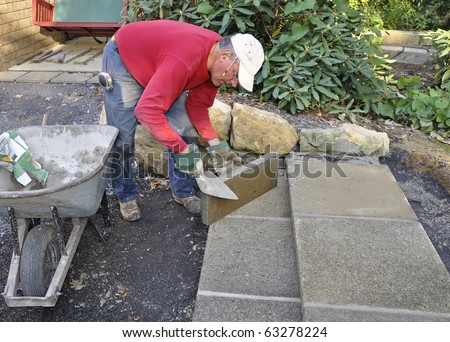 Man building patio steps using concrete pavers - stock photo