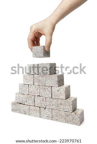 Man building pyramid made of small blocks of granite rock. - stock photo