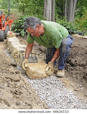 Man building stone wall - stock photo