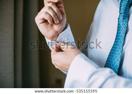 Man buttoning on the sleeve of his shirt. Zip up the cufflink. Men's style.