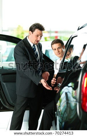 Man buying a car in dealership sitting in his new auto, the salesman talking to him and explaining details
