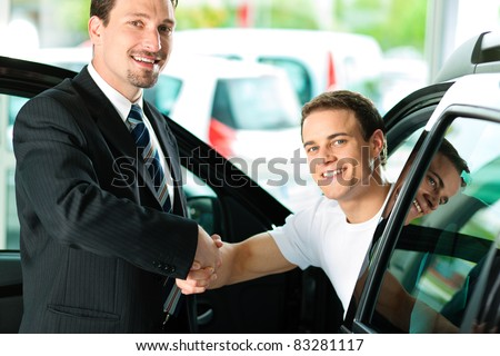 Man buying a car in dealership sitting in his new auto; they are shaking hands to close the deal - stock photo