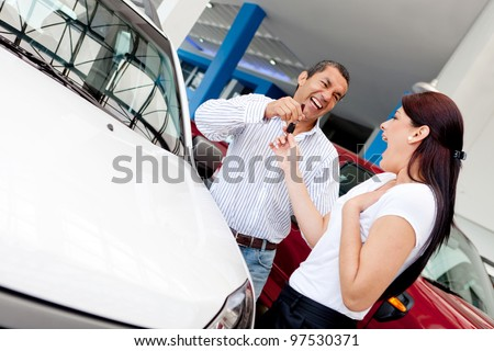 Man buying car to his wife and giving her the keys - stock photo