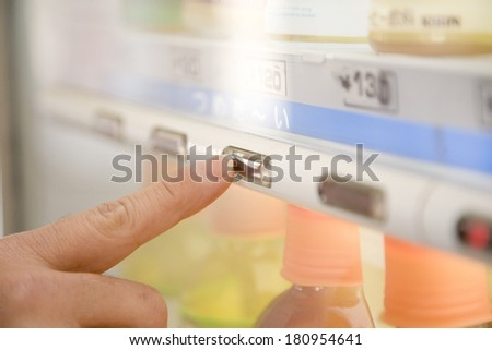 man buying drinks from a vending machine - stock photo