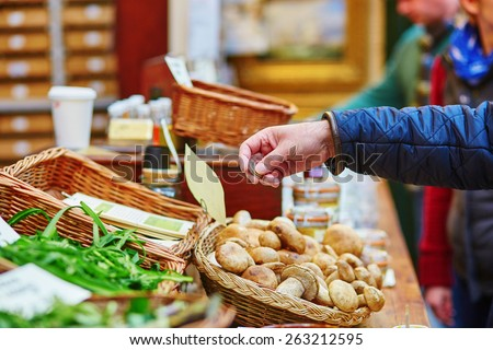 Man buying fresh mushrooms on London farmer agricultural market - stock photo