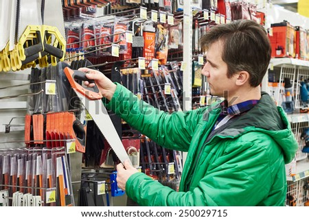 Man Buying Handsaw In Hardware Store