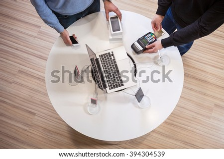 Man buying smartphone and paying with credit card using terminal - stock photo