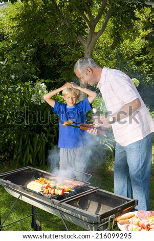 Man by barbeque showing son sausage, smiling - stock photo