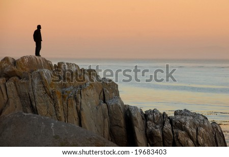 Man by himself on cliff overlooking sea - stock photo
