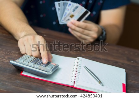man calculate how much cost or spending have with credit cards - stock photo