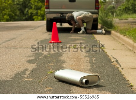 man calling for help after muffler detaches from vehicle - stock photo