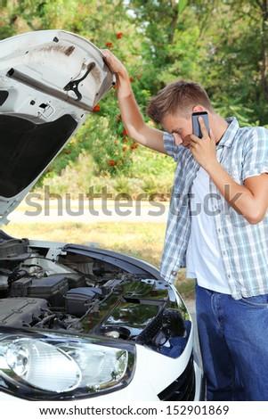 Man calling repair service after car breakdown - stock photo