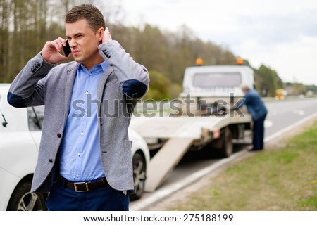 Man calling while tow truck picking up his broken car  - stock photo