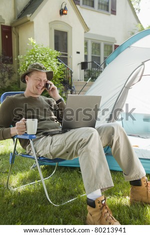 Man camping in his front yard with laptop computer and cell phone - stock photo