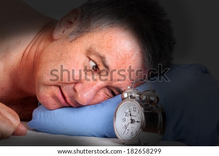 Man can not sleep and looked at the alarm clock - stock photo