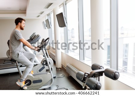Man cardio training on a bicycle in a gym - stock photo