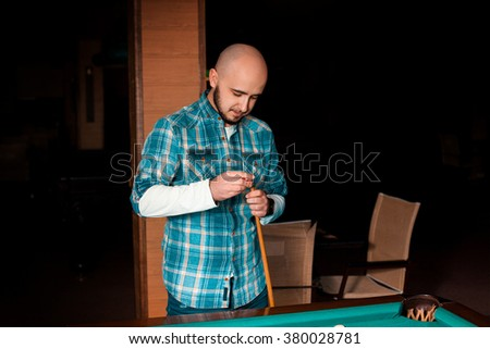 man carefully prepares his cue with chalk to hitting. American pool billiard. Pool billiard game. Billiard sport concept. - stock photo