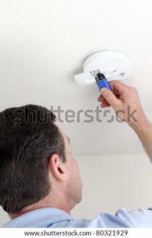 Man carefully replacing 9 volt battery in round white ceiling smoke alarm detector for the safety of his household. - stock photo